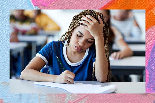 A imagem mostra uma menina negra, com o cabelo longo e escuro em tranças. Ela está usando o que parece ser um uniforme escolar, com uma camiseta azul com a ponta das mangas e a gola brancas. Ela está sentada em uma mesa, escrevendo em uma folha com uma mão enquanto a outra apoia a cabeça, como se estivesse pensando. No fundo, mesmo que levemente desfocado, é possível ver outras carteiras e pessoas atrás dela, como se estivesse numa escola ou numa sala de prova.