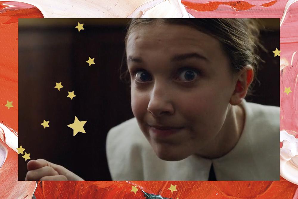 Foto de Millie Bobby Brown em cena de Enola Holmes; a atriz está com os olhos arregalados e pressionando os lábios sorrindo levemente com o cabelo preso e repartido ao meio; a moldura é uma textura de tintas em tons de rosa, vermelho e branco com estrelas amarelas de decoração