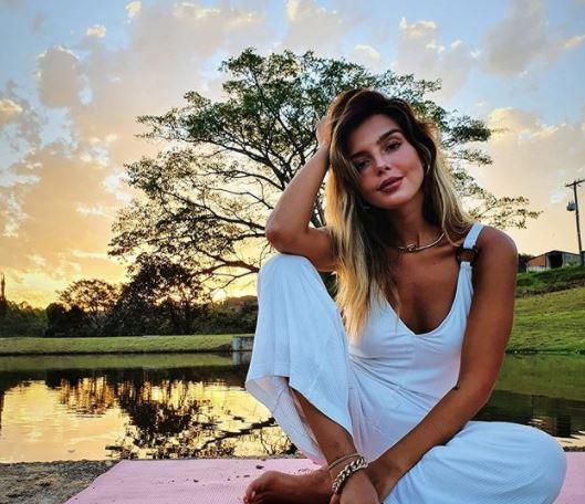 Giovanna Lancelotti posando para foto em uma paisagem natural com lago e pôr-do-sol de fundo com uma árvore e grama; ela está sentada uma roupa branca, o cotovelo apoiado no joelho e cabeça apoiada na mão