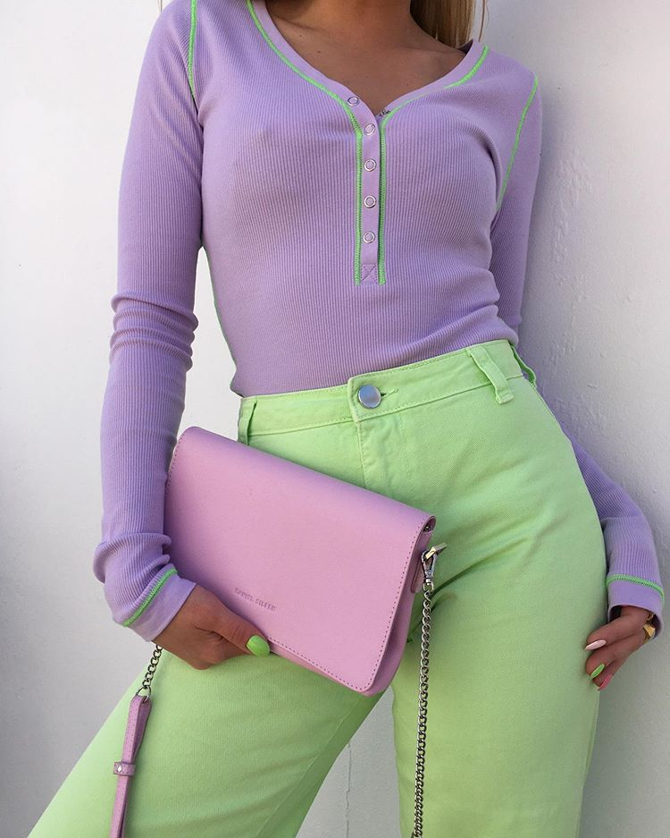 Foto mostrando corpo de uma garota da altura do joelho até o pescoço. Ela está usando uma blusa de manga comprida lilás, uma calça verde pastel e segurando uma bolsa rosa pastel.