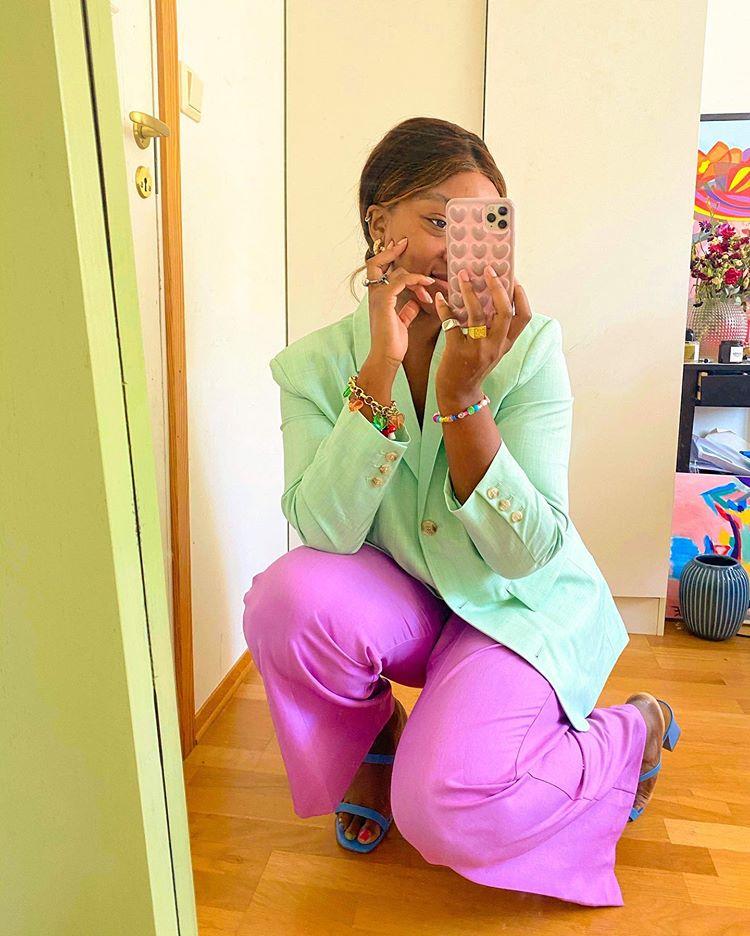 Garota abaixada em frente ao espelho com celular cobrindo o rosto para tirar foto. Ela está com um blazer verde pastel, uma calça lilás e uma sandália azul.