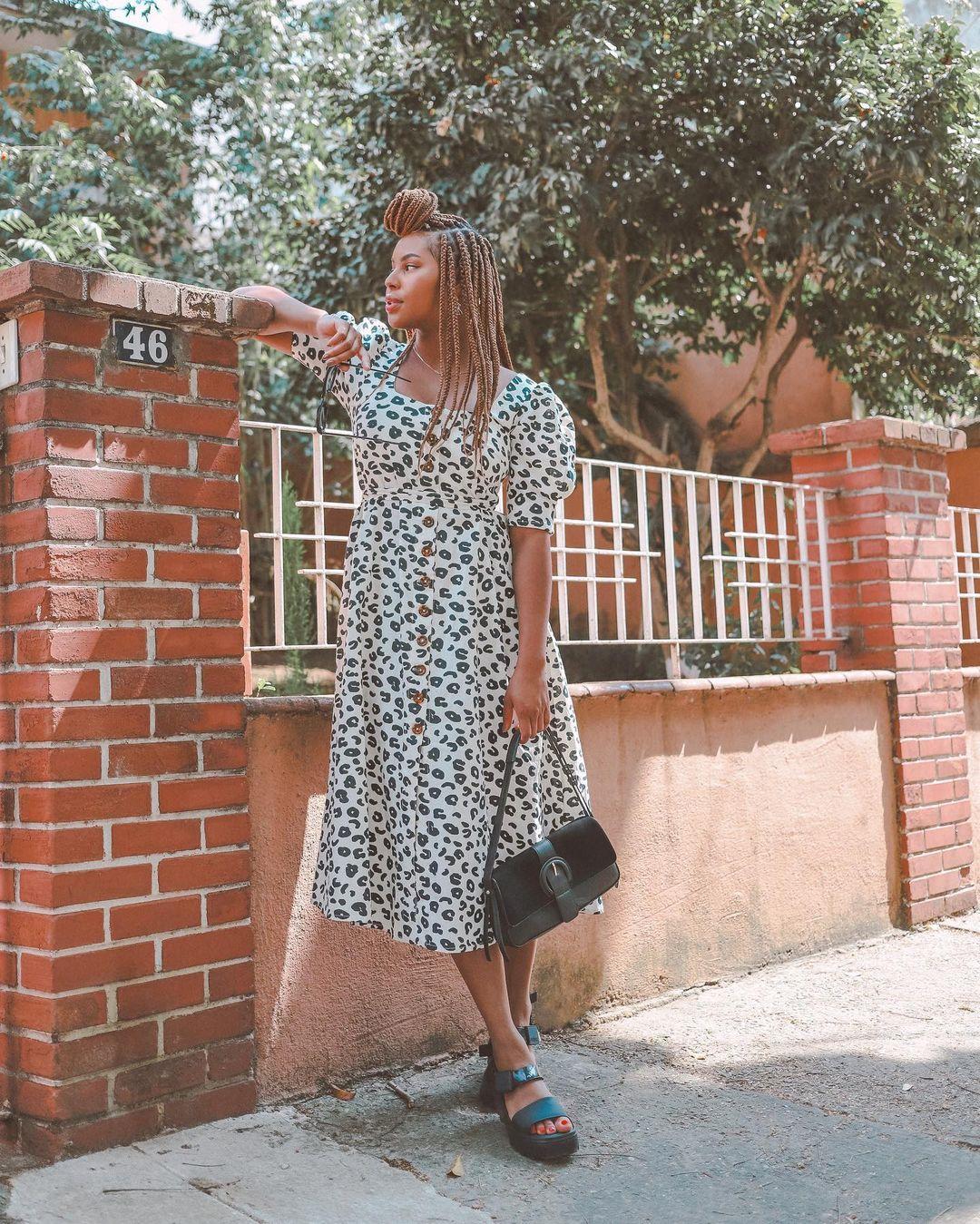 Garota usando vestido com estampa de oncinha preta e branca, segurando uma bolsa preta e usando uma sandália preta. Ela está olhando para o lado, com uma das mãos apoiadas em uma mureta de tijolinhos.