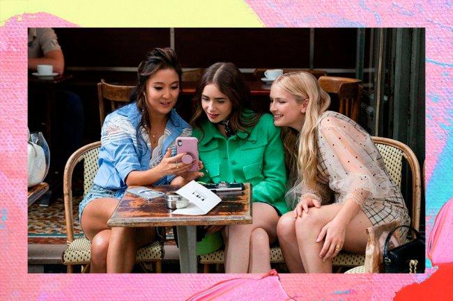Mindy, Emily e Camille, sentadas diante de uma mesa quadrada. Todas elas estão olhando curiosas para um celular