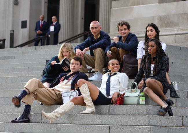 Elenco do reboot de Gossip Girl sentados na escadaria do MET, em Nova Iorque. Alguns atores estão olhando para tela ou sorrindo enquanto outros estão com expressões sérias
