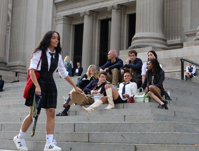 Elenco do reboot de Gossip Girl sentados na escadaria do MET, em Nova Iorque. Alguns atores estão olhando para tela ou sorrindo enquanto outros estão com expressões sérias. Uma da protagonista está passando por eles no primeiro plano da imagem