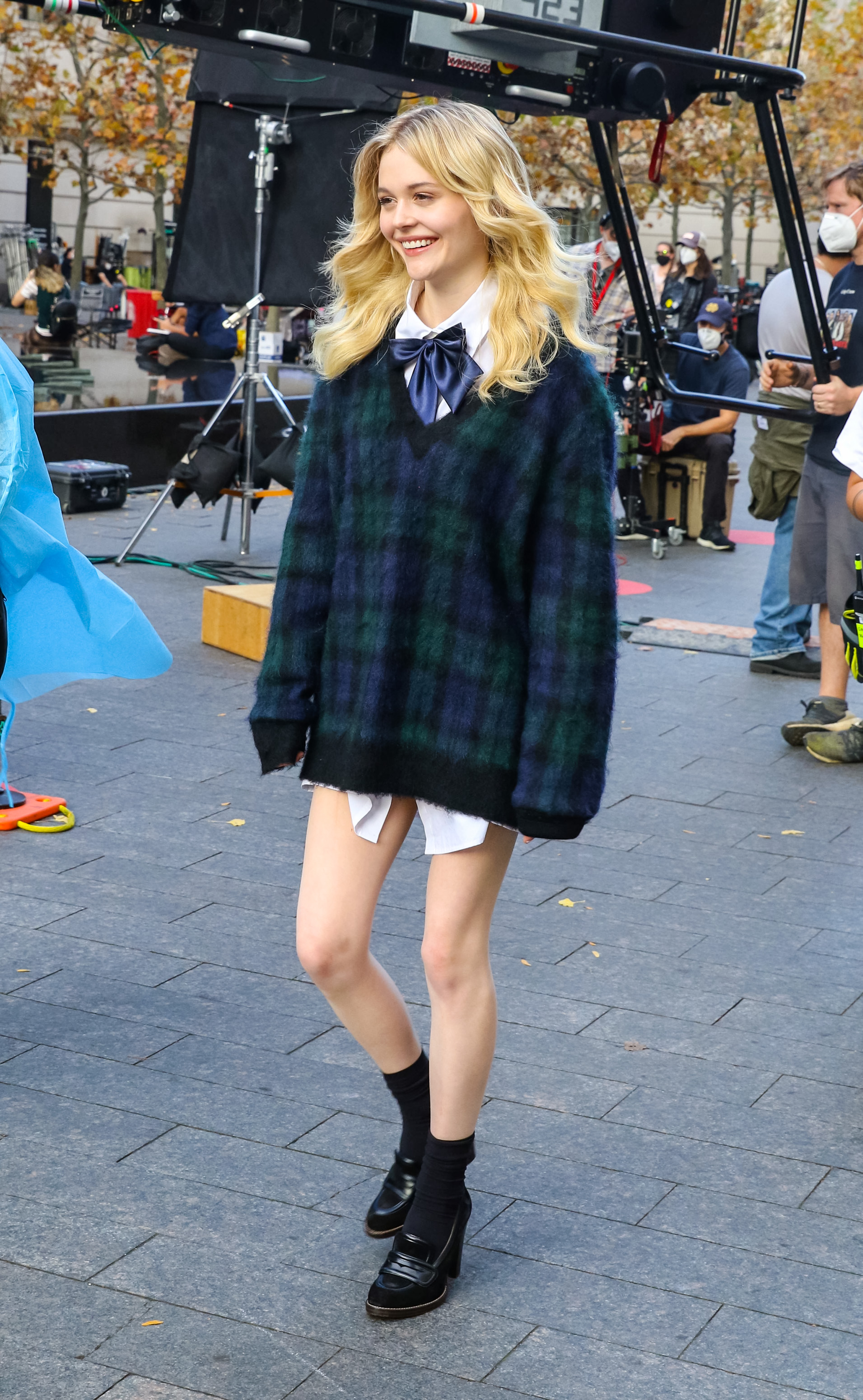 Emily Alyn Lind nas gravações da nova Gossip Girl. Ela está usando um suéter xadrez por cima de uma camisa branca, um oxford preto de salto com meia preta. Ela está sorrindo enquanto anda e não olha para a câmera.