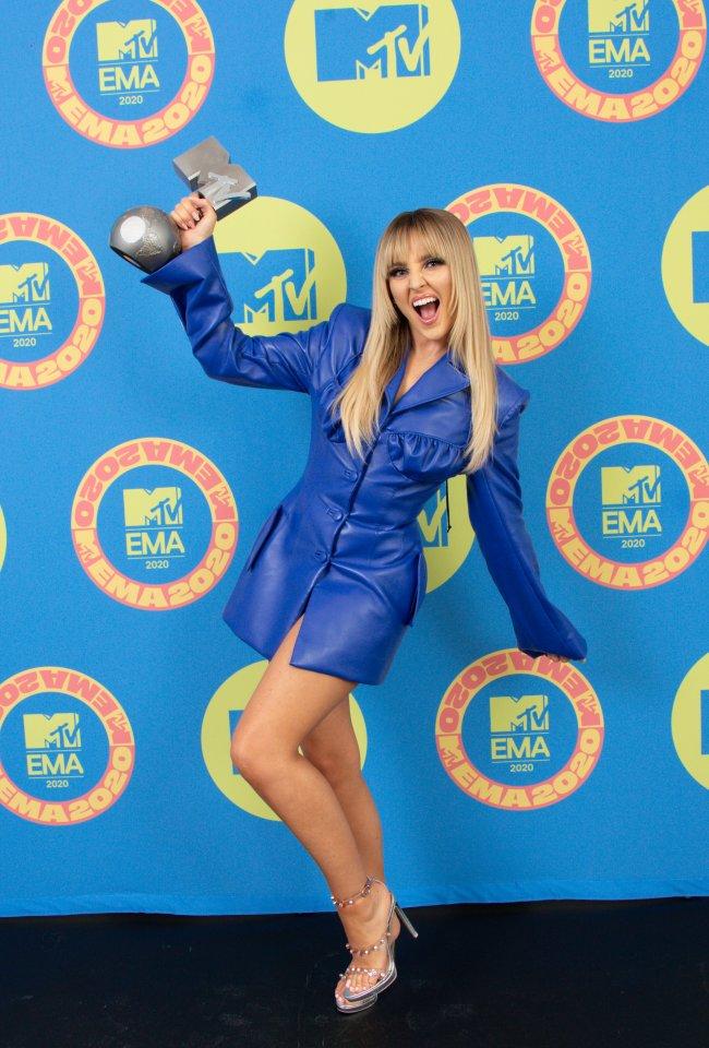 Perrie Edwards de franjinha posando com prêmio no MTV EMA de 2020; ela usa um look azul escuro e levanta o troféu com uma das mãos