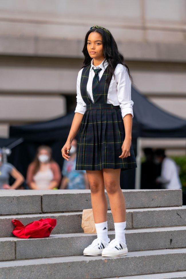 Whitney Peak nas gravações do reboot de Gossip Girl usando camisa branca, gravata, salopete xadrez e tênis branco