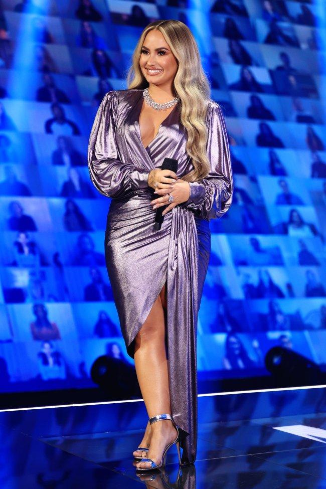 Demi Lovato no E! People's Choice Awards usando vestido roxo, um colar brilhante e salto prata sorrindo e segurando um microfone preto