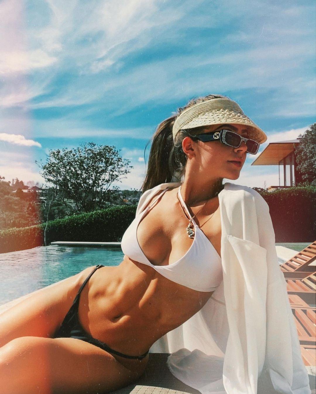 Jade Picon usando biquíni preto e branco com viseira e camisa