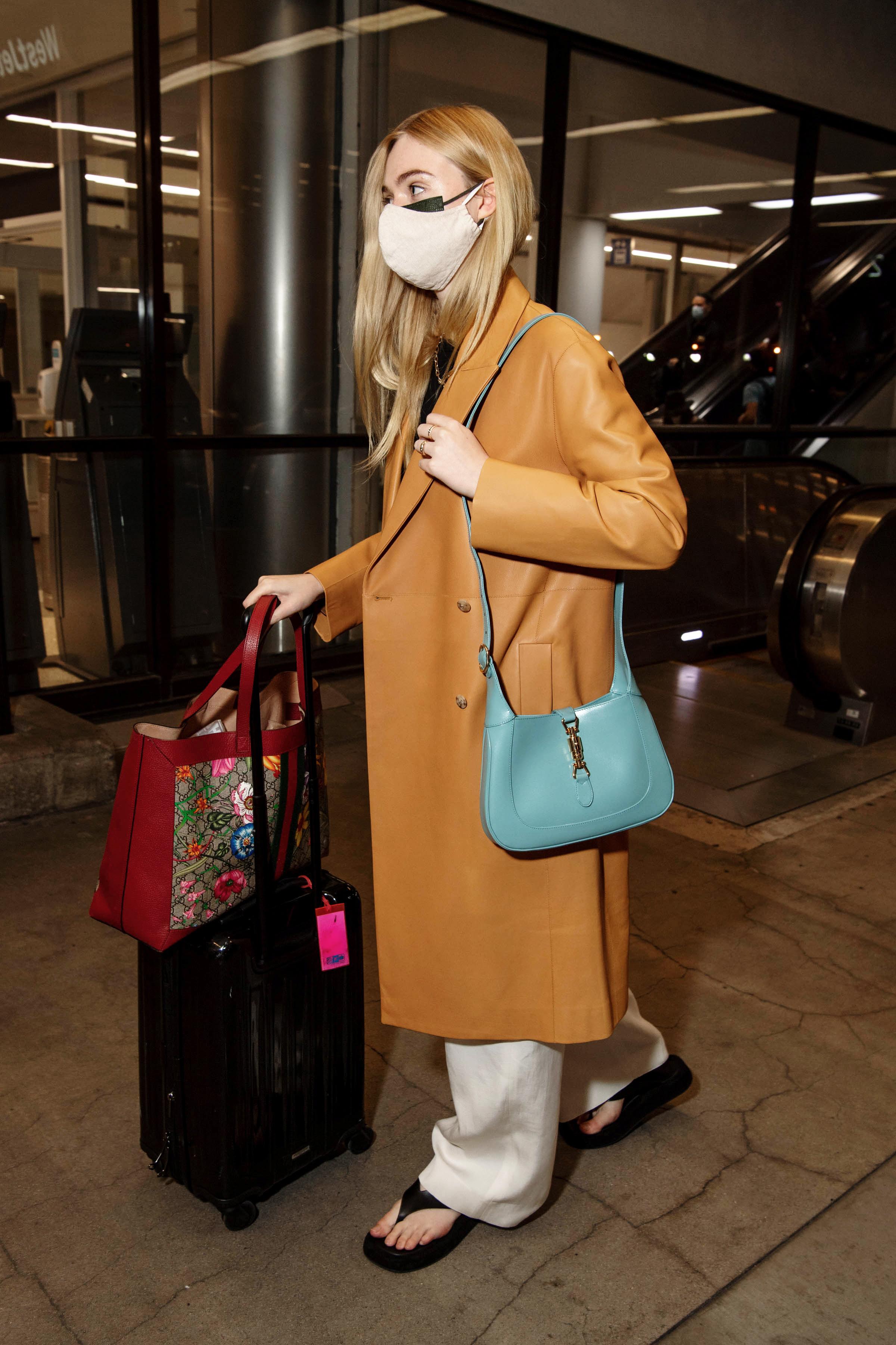 Elle Fanning usando chinelo de plataforma preto com calça branca, casaco marrom e bolsa azul