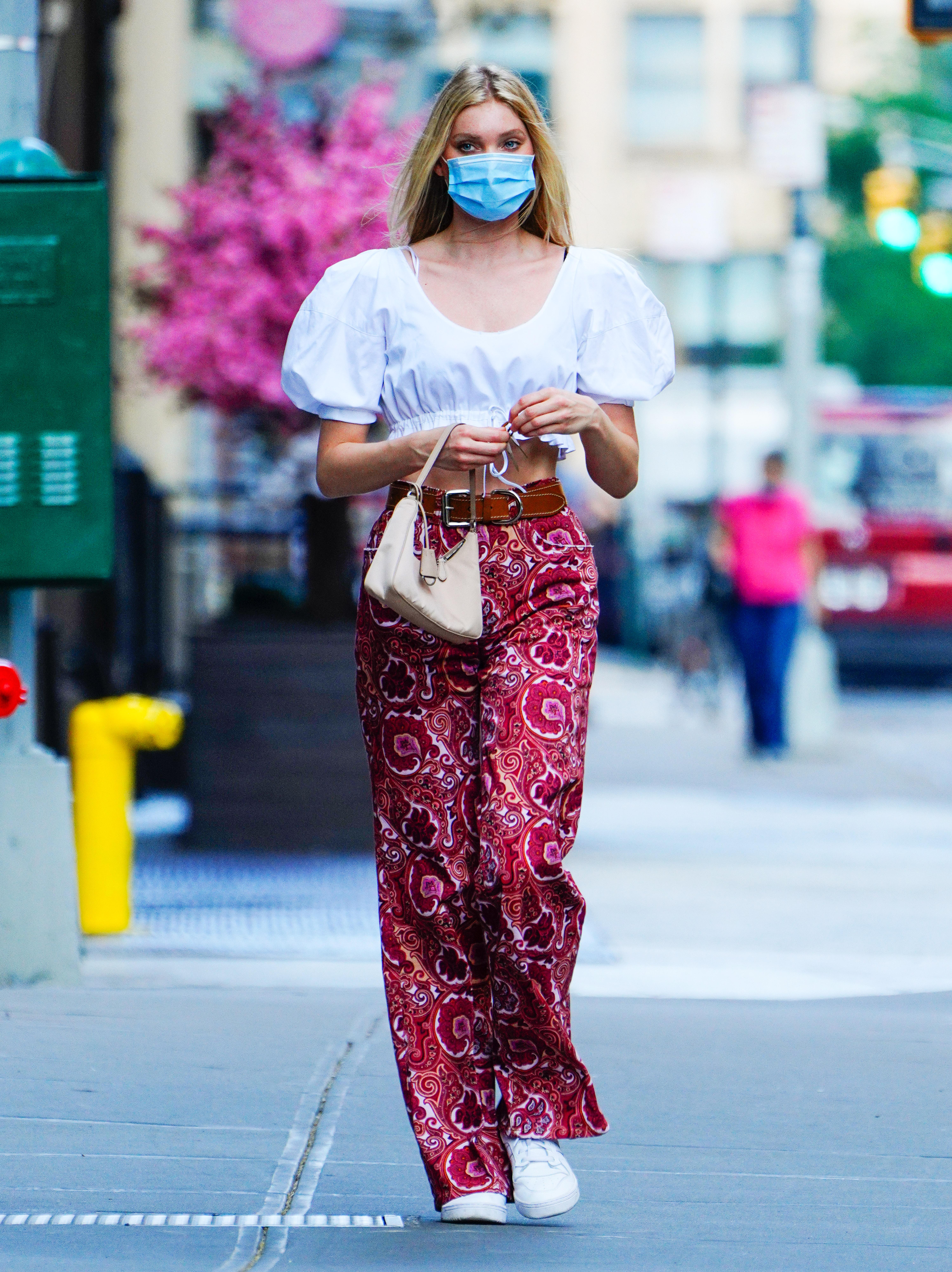 Elsa Hosk usando top cropped branco de mangas bufantes, calça vermelha com estampa paisley e tênis branco. Ela segura uma bolsinha rosa pastel em uma das bolsas e usa uma máscara de proteção azul e branca no rosto.