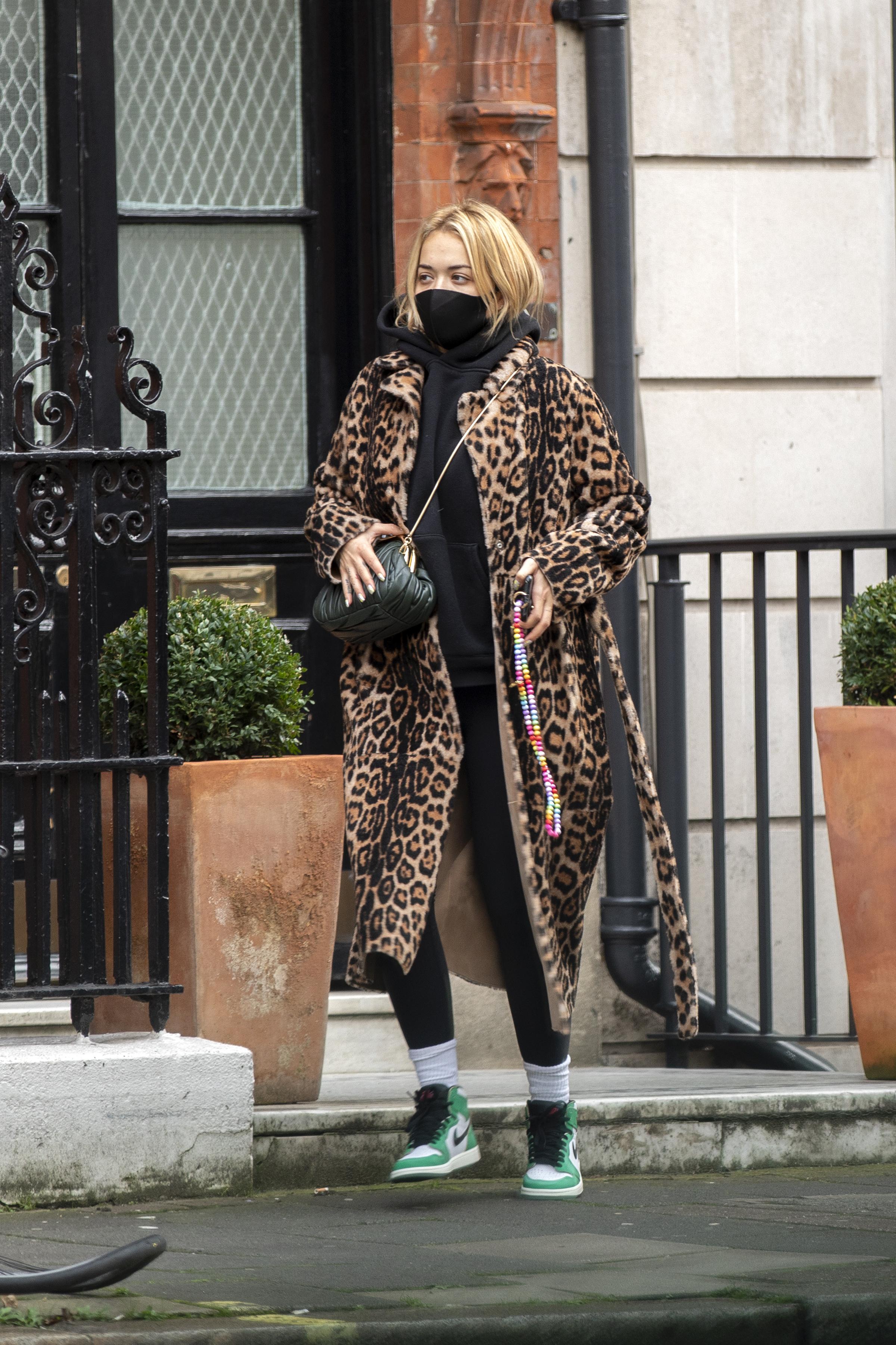 Rita Ora usando look com moletom preto, calça legging preta, tênis verde e branco de cano alto, sobretudo com estampa de oncinha e bolsa preta atravessada no ombro. Ela está com máscara de proteção preta, olhando para o lado, em uma pose espontânea.