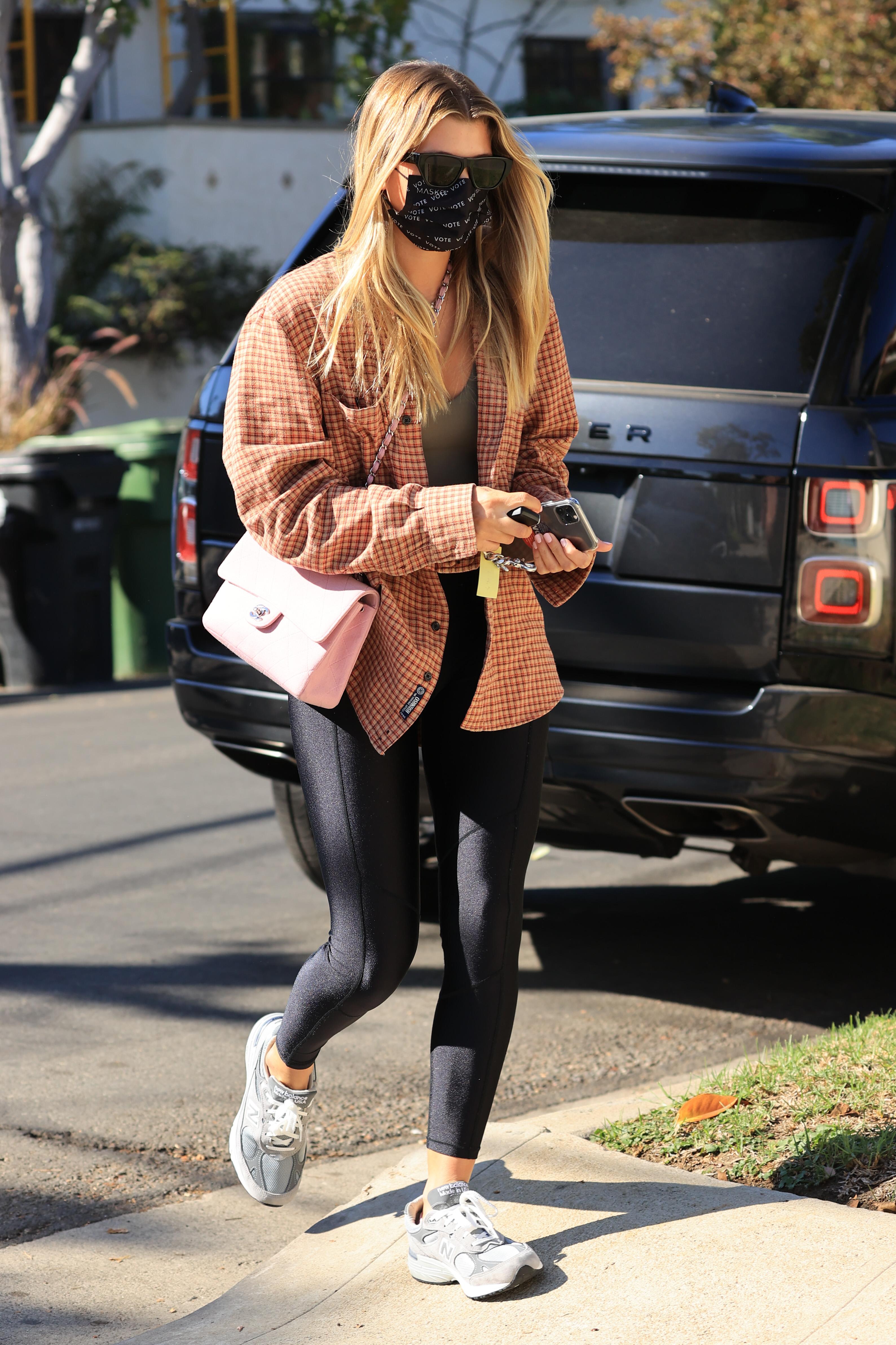 Sofia Richie usando legging e tênis com camisa xadrez e bolsa rosa da Chanel