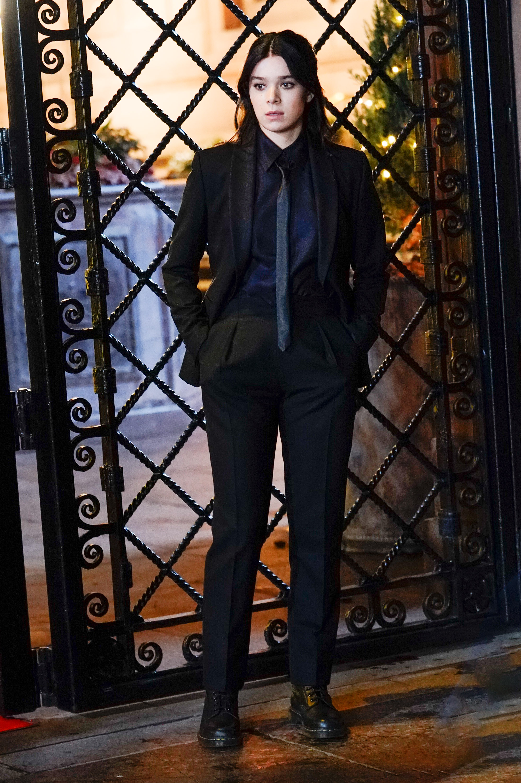 Hailee Steinfeld usando terninho preto formado por camisa, blazer, gravata e calça de alfaiataria com um coturno