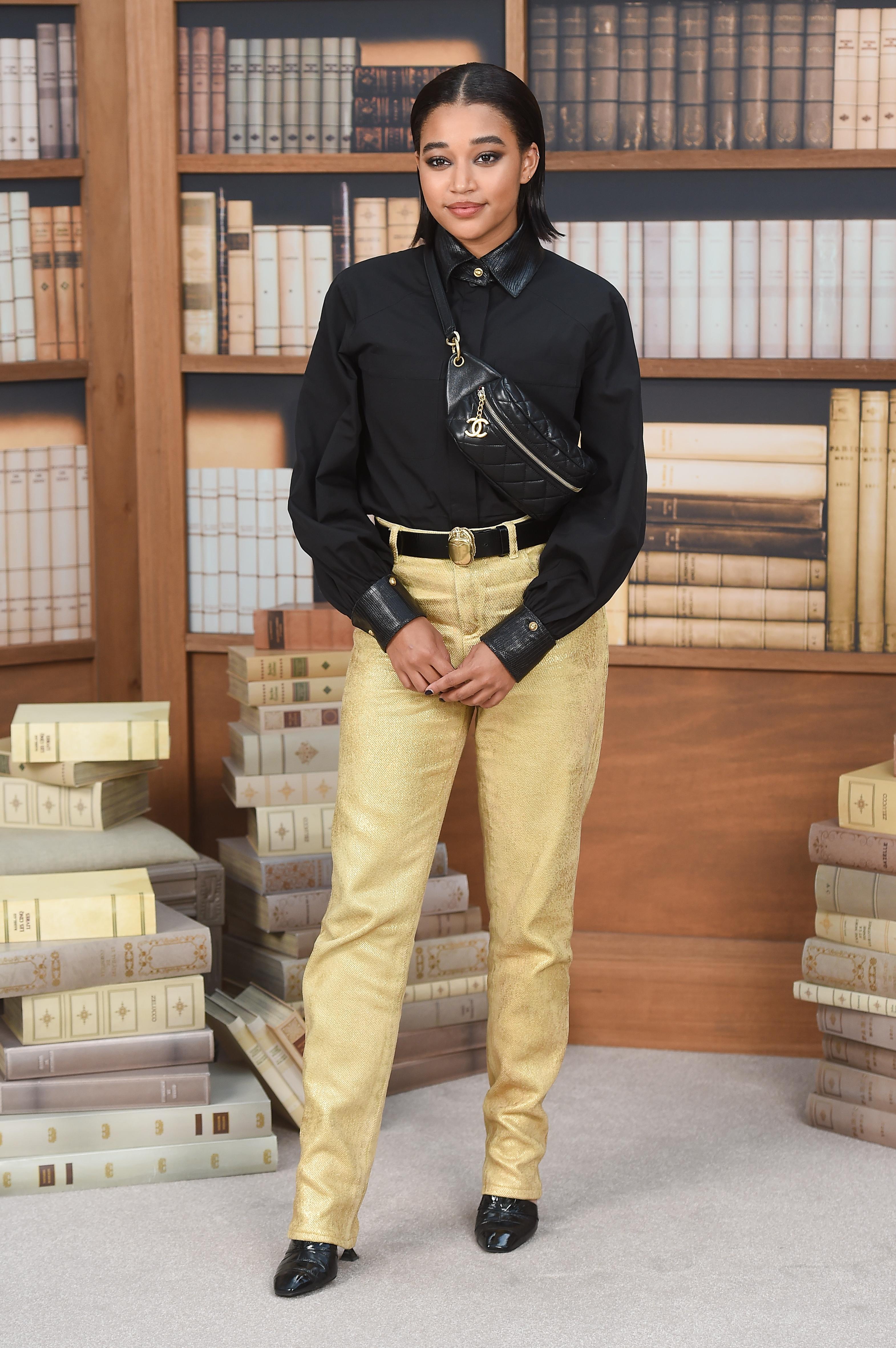 Amandla Stenberg usando camisa preta, pochete preta da Chanel, cinto preto e dourado, calça dourada de alfaiataria e mocassim preto com salto