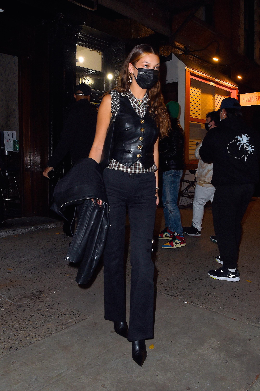 Bella Hadid usando colete de couro por cima de camisa xadrez de manga curta, calça jeans e bota preta de bico fino