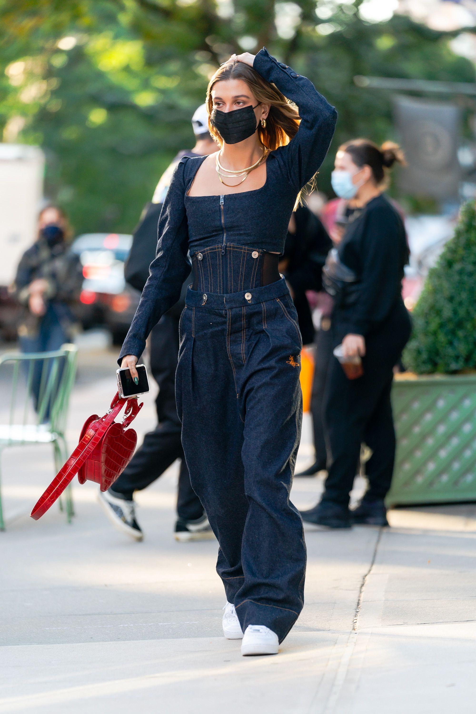 Hailey Bieber usando look todo jeans com bolsa vermelha de coração e tênis branco