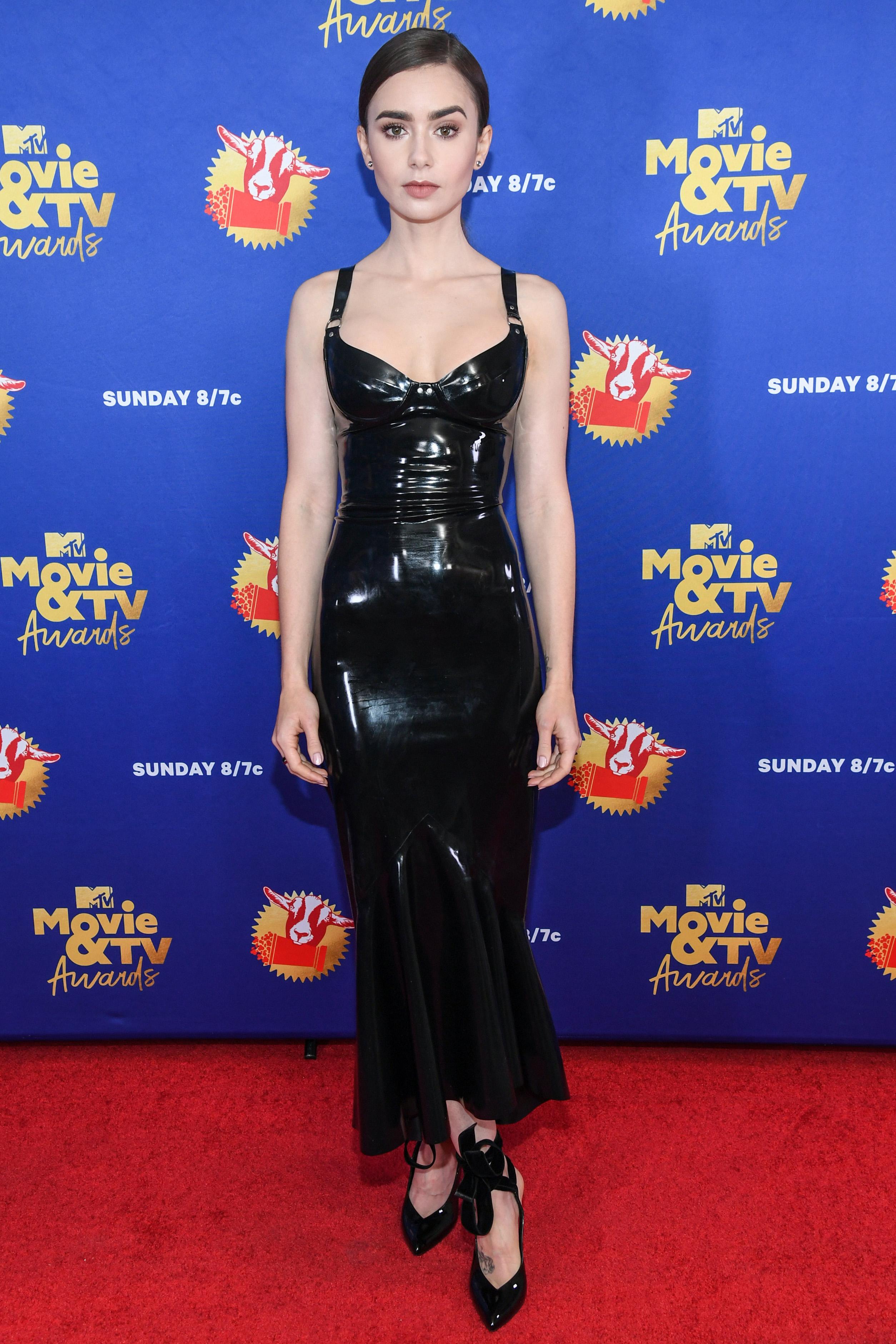 Lily Collins usando vestido preto de látex com scarpin preto de vinil