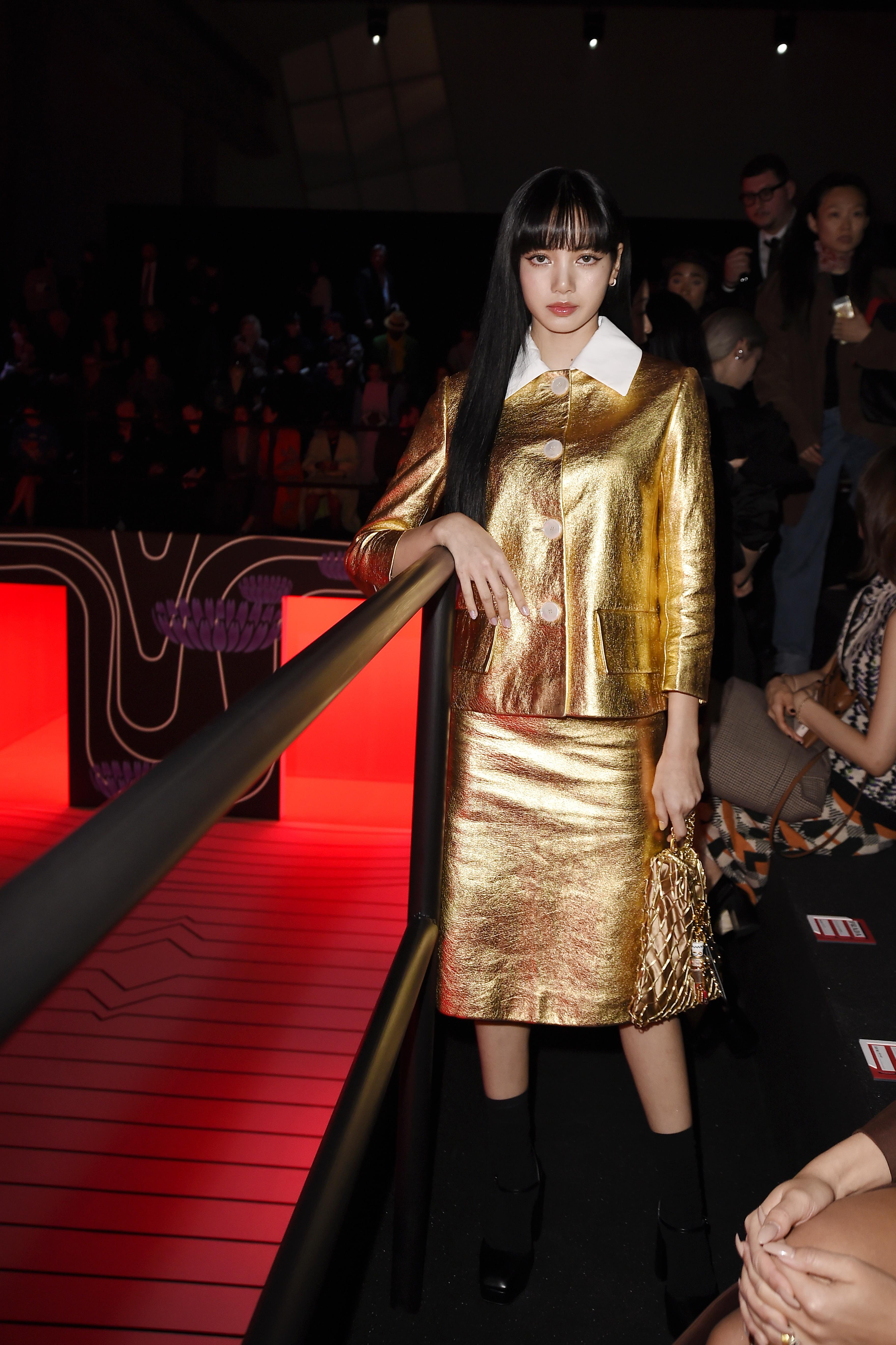 Lisa usando camisa de botões douradas, com saia abaixo do joelho e bolsa douradas e sapato preto com meia preta