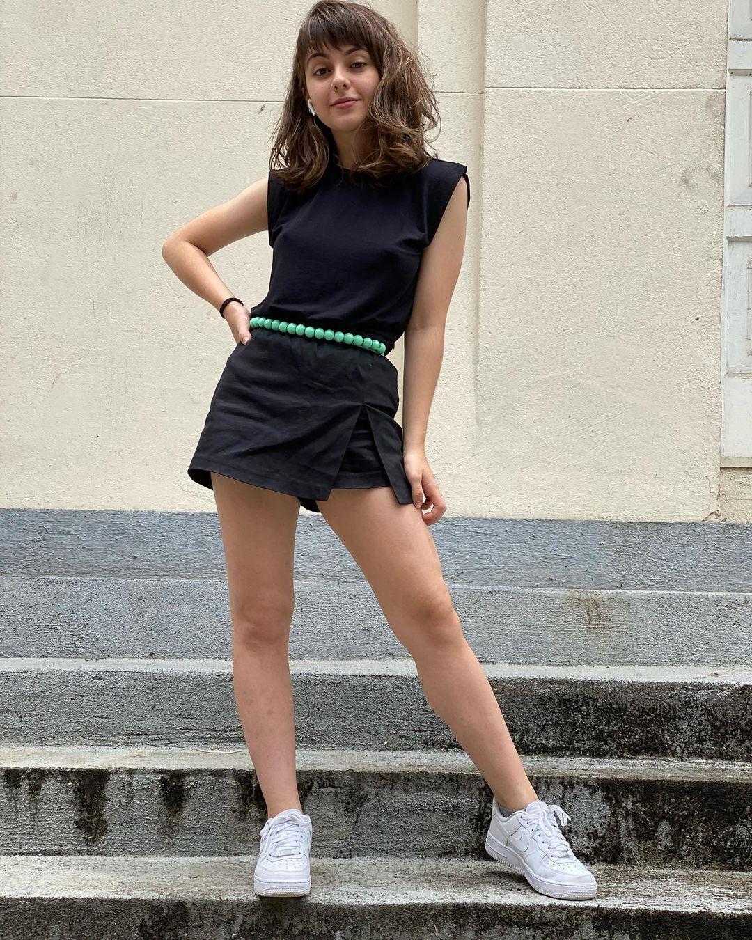 Klara Castanho usando muscle tee preta com short saia preto, tênis branco e cinto verde