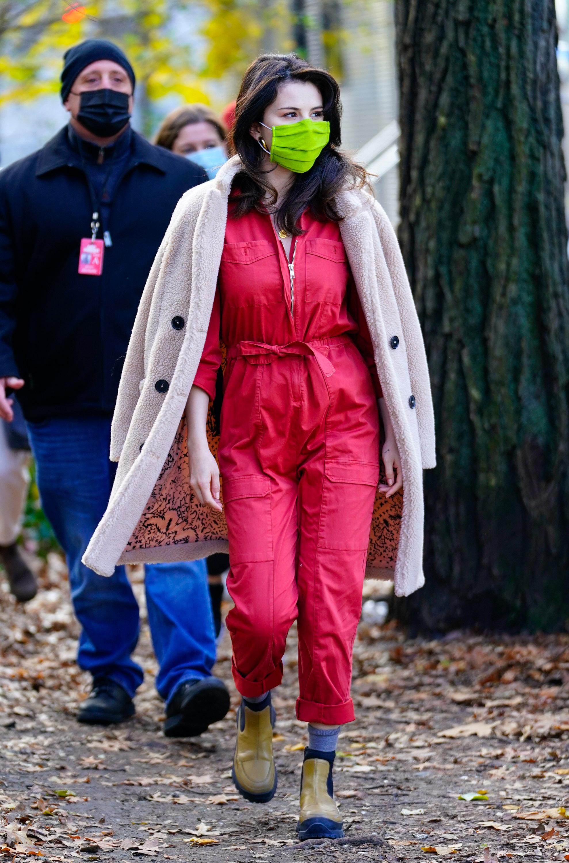 Selena Gomez usando macacão vermelho com bota marrom, meia cinza e sobretudo bege