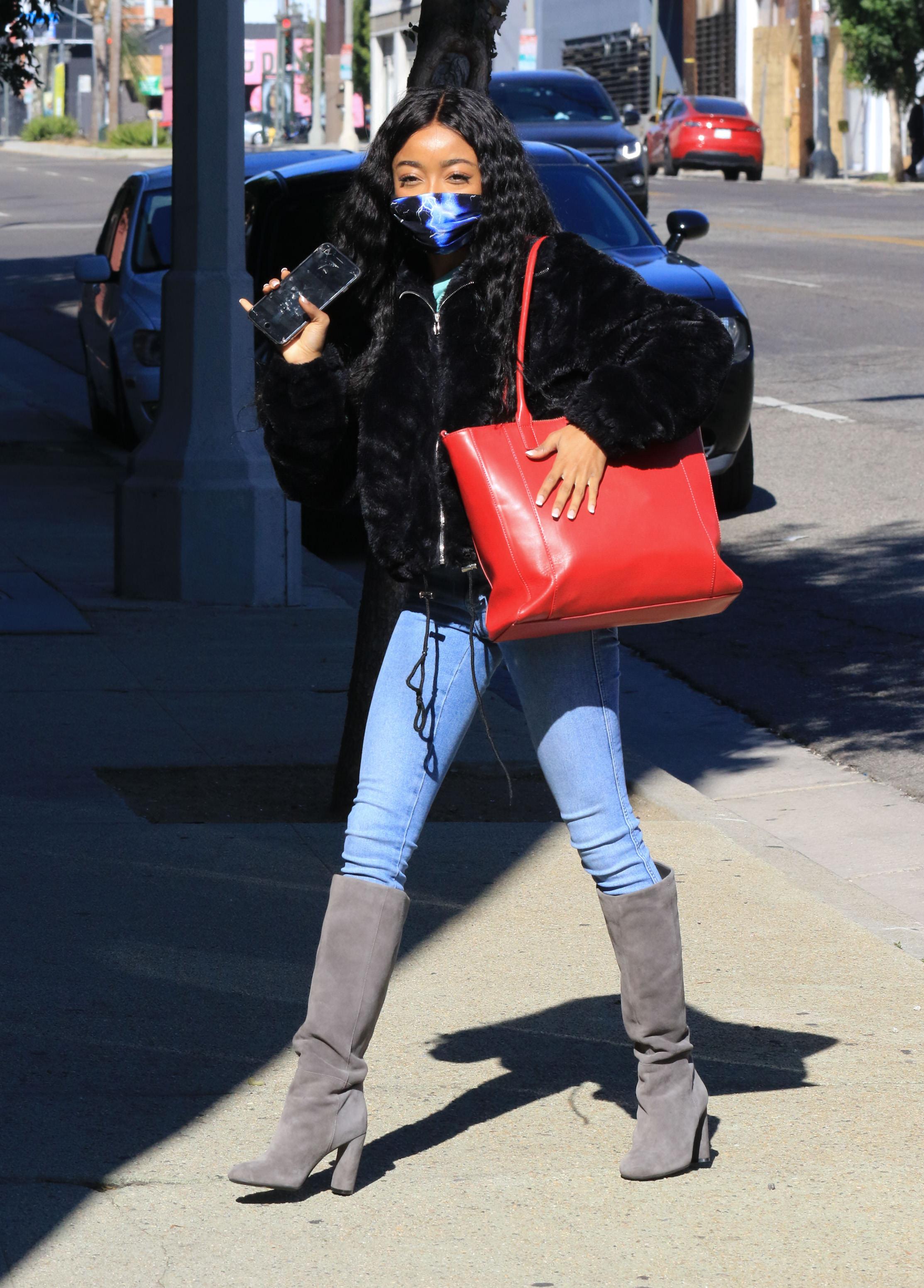 Skai Jackson usando casaco de pelos preto, calça jeans e bota cinza por cima
