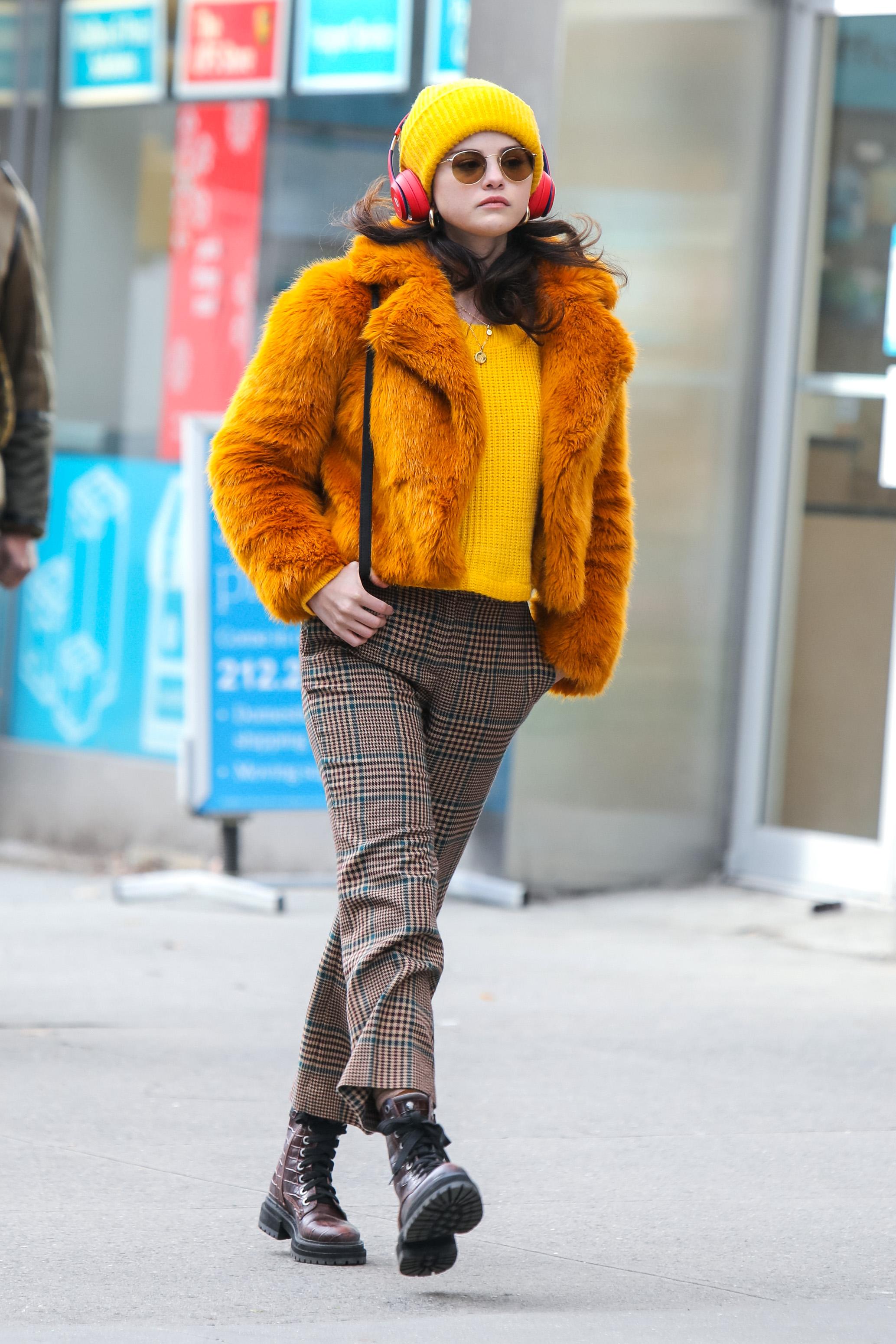 Selena Gomez usando suéter e gorro amarelos, casaco de pelos laranja, calça xadrez, coturno e óculos de sol