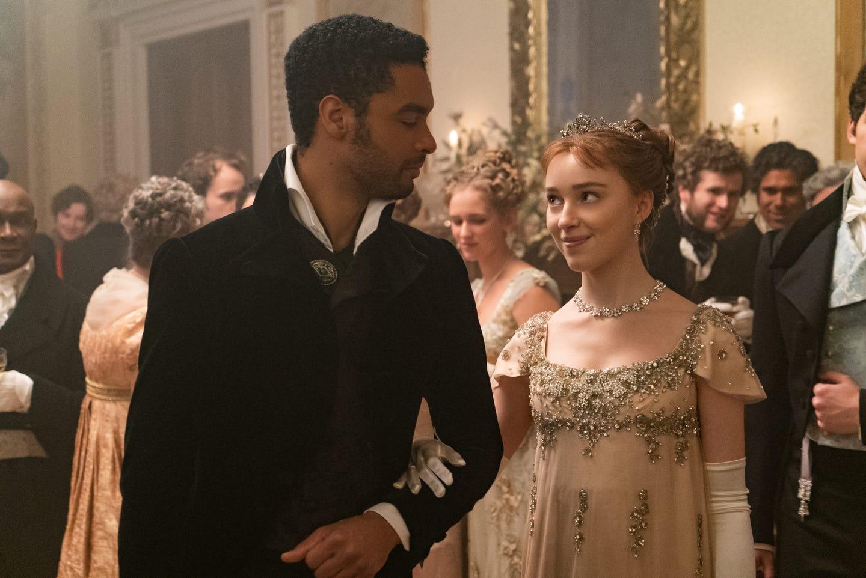 Cena de Bridgerton em que Simon olha para Daphne e ela está com o braço estrelaçado com o dele