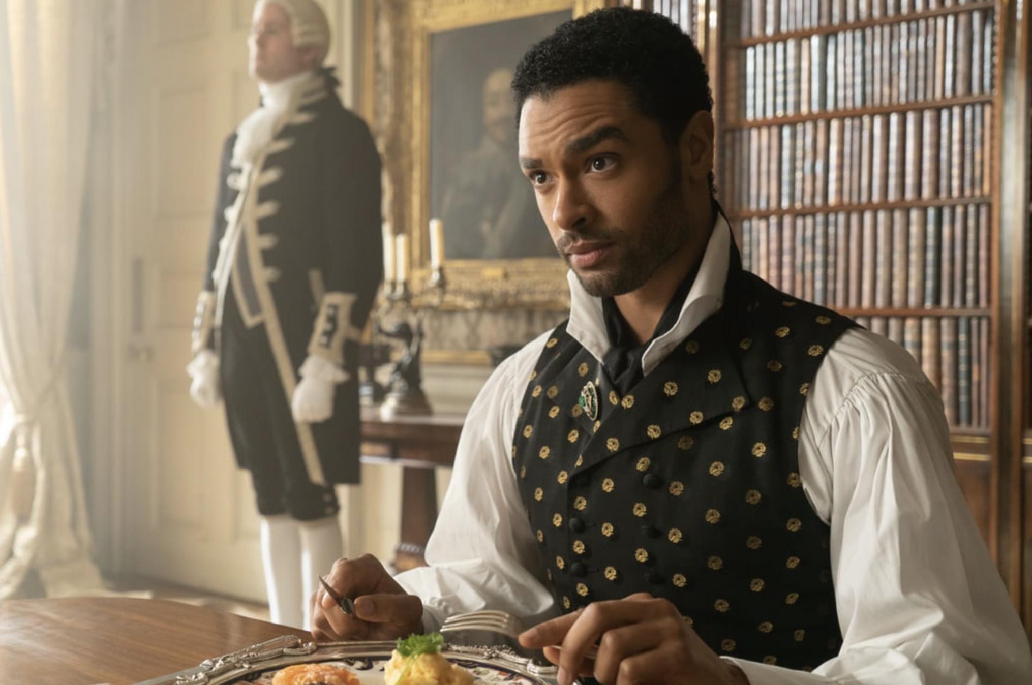 Regé-Jean Parege como Simon Basset na série Bridgerton, está em uma mesa, segurando os talheres diante da refeição e olhando para frente.