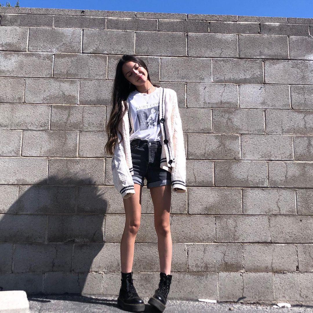 Olivia Rodrigo usando short e coturno pretos, camiseta branca e casaco bege