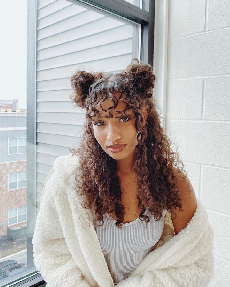 Garota com cabelo cacheado e franja usa penteado com dois pequenos coques