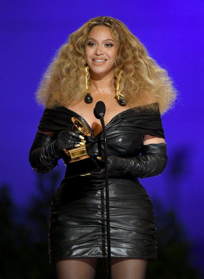 Beyoncé sorrindo e fazendo um discurso no Grammy 2021. Ela segura um prêmio
