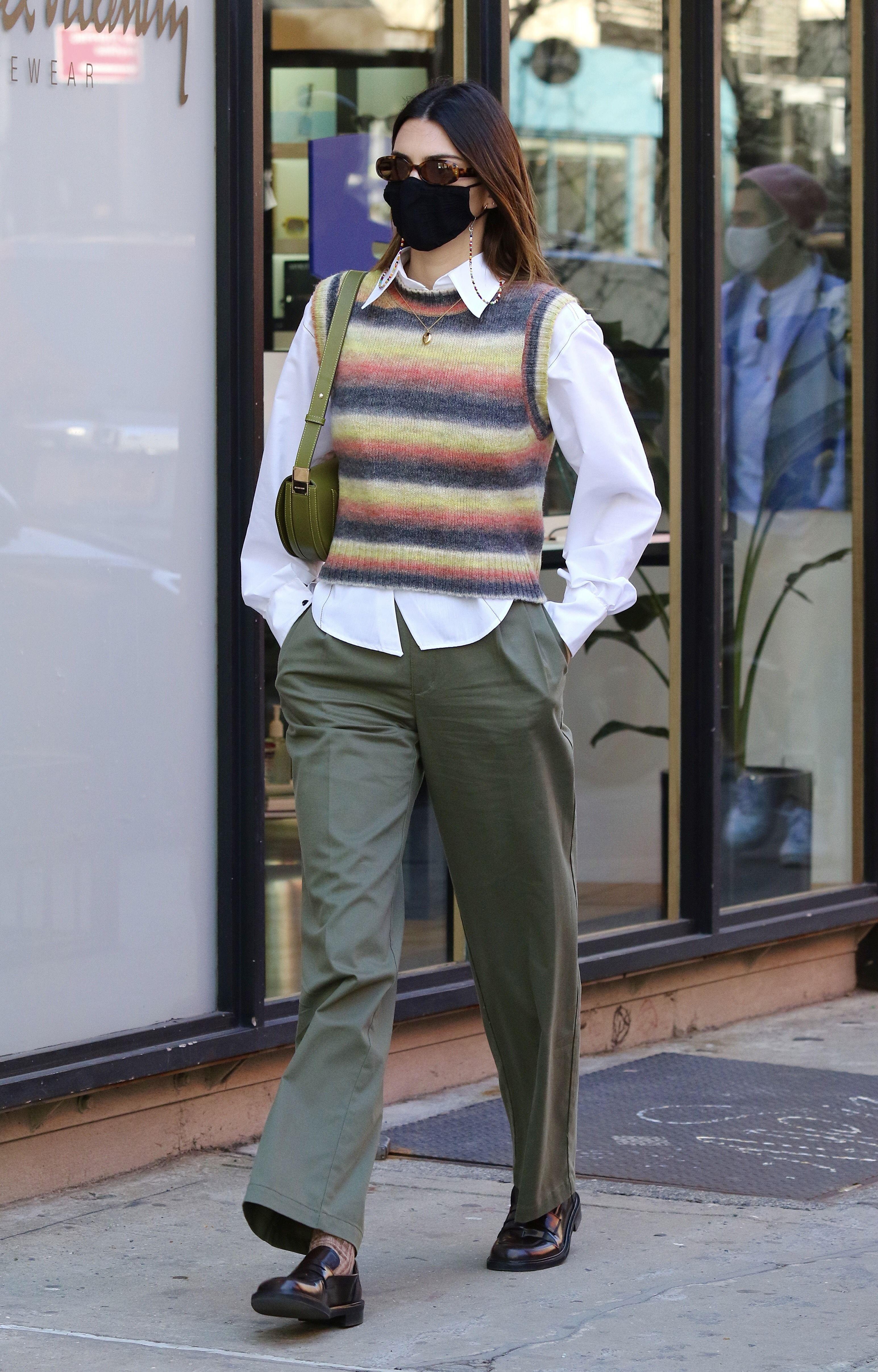 Kendall Jenner usando colete listrado por cima de camisa branca com calça verde e sapato oxford