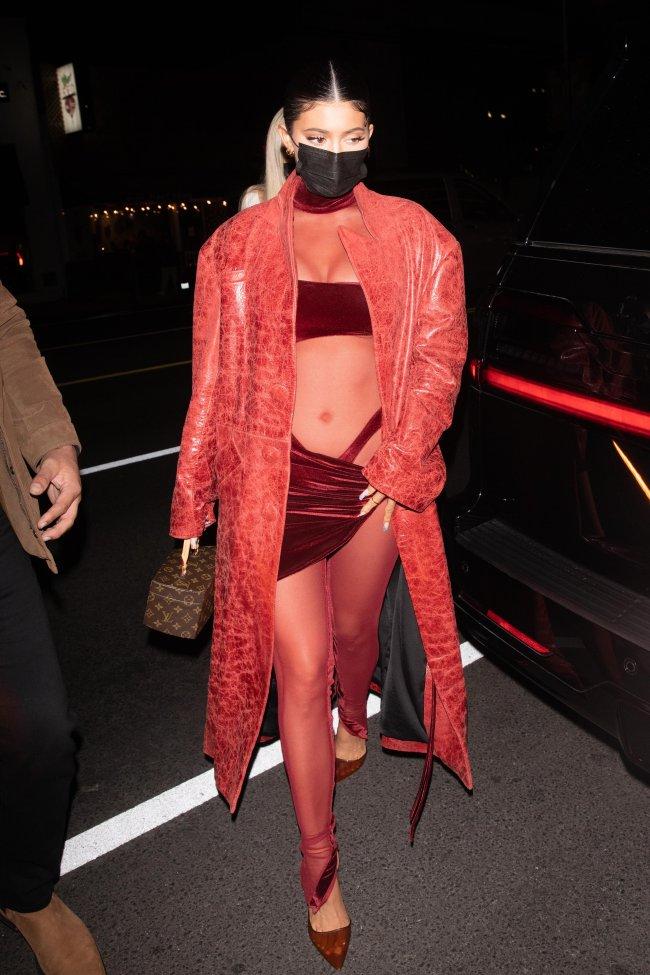 Kylie Jenner de máscara no rosto, usando macacão vermelho e transparente, com alça da calcinha à mostra com um casaco por cima