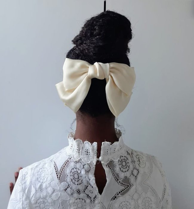 garota de costas com o cabelo preso em um coque amarrado com um laço branco