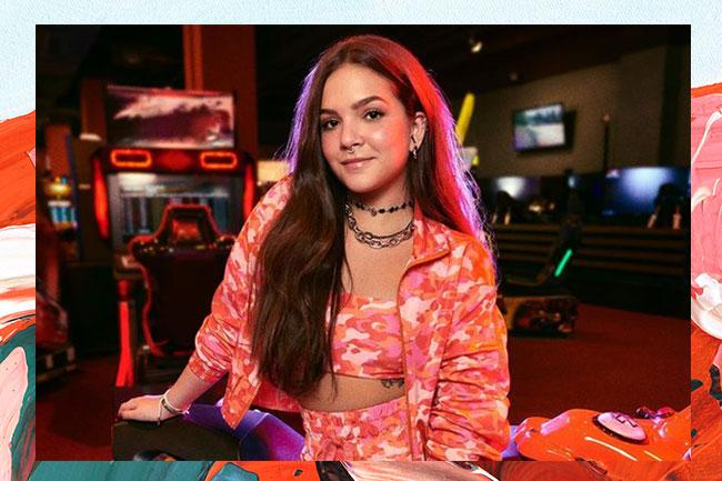 Mel Maia usando conjuntinho laranja e sorrindo levemente para a câmera