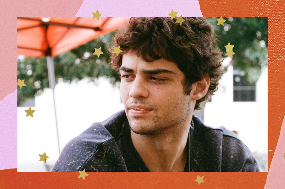 Noah Centineo olhando para o lado com expressão séria; o ator usa uma blusa preta