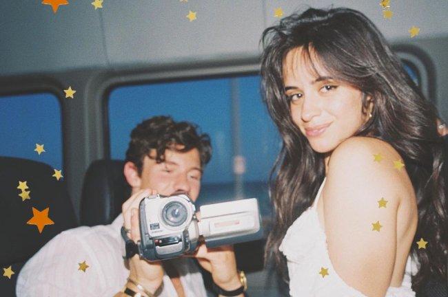 Shawn Mendes e Camila Cabello. Ela olha de lado e sorri enquanto ele segura uma câmera