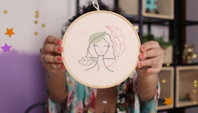 Mulher segura bastidor branco com desenho de um bordado de uma jovem com cabelo curto. Não conseguimos ver o rosto de quem segura o bordado, mas, conseguimos ver suas unhas pintadas de vermelho e sua camisa com detalhes florais.