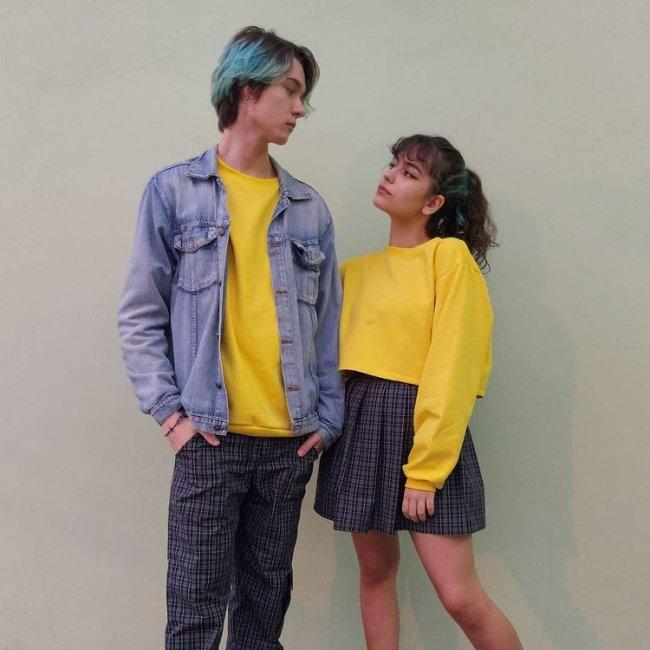 Jovem casal se olhando, enquanto o rapaz utiliza uma jaqueta jeans com camiseta amarela e calça xadrez, e a menina utiliza blusa de moletom amarela e saia com a mesma estampa do rapaz.