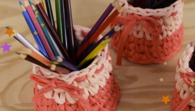 Dois porta lápis de crochê com tom laranja e branco, com lápis coloridos dentro, posicionados em cima de uma mesa de madeira clara.