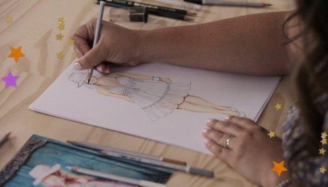 Na imagem vemos uma mesa com canetas, lápis e uma folha sendo desenhada por alguém. O desenho é um croqui de moda.