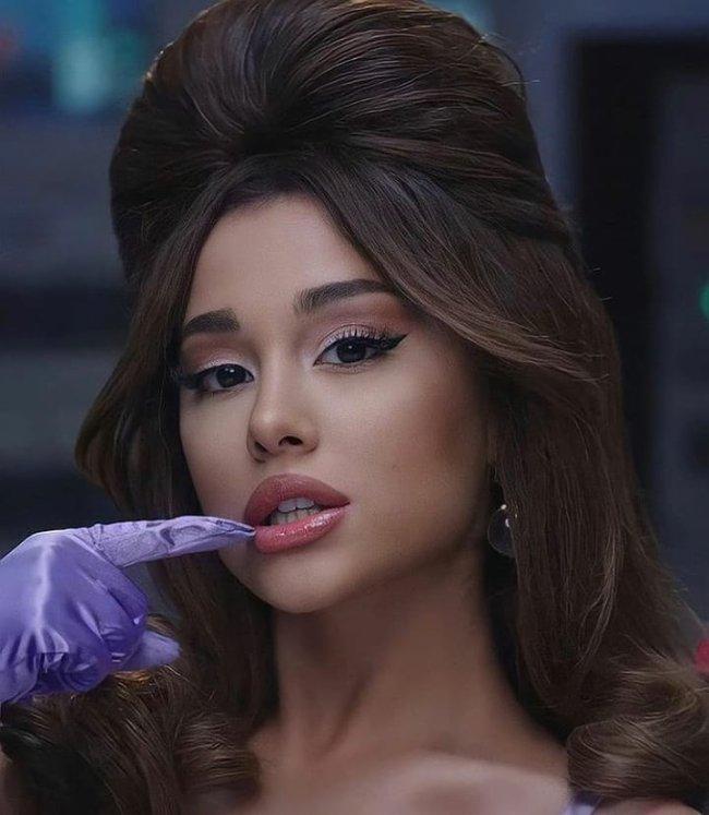 Ariana Grande posando para foto com cabelo com topete, usando luva lilás e com um dos dedos apoiados na boca. Encarando a câmera com um olhar sério.