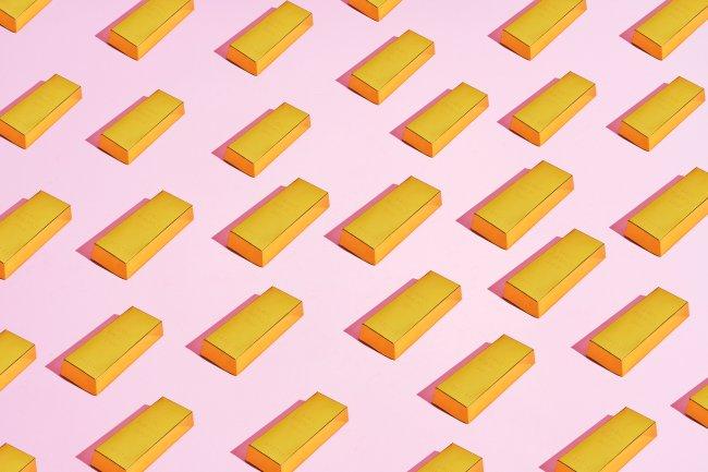 Ilustração de várias barrinhas de ouro em cima de um fundo rosa claro