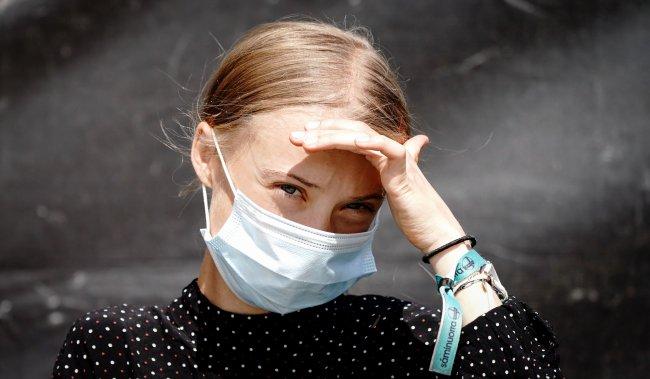 A ativista pelo clima Greta Thunberg usando máscara de proteção contra o coronavírus e usando a mão para se proteger so Sol