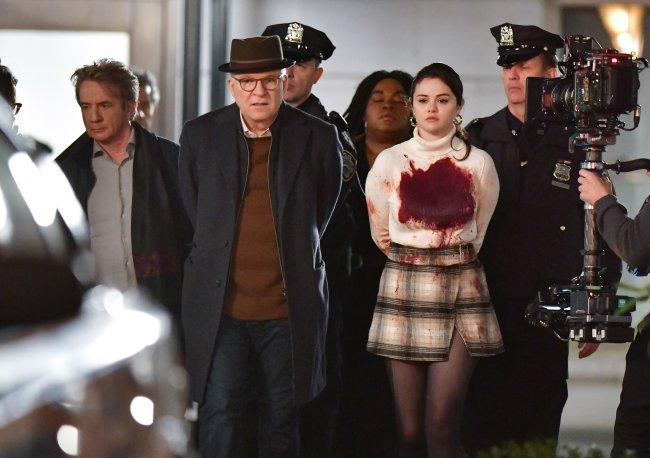 Ator Martin Short, Steve Martin e Selena Gomez sendo escoltados pela polícia, todos com os braços para tras, no set de filmagem da série