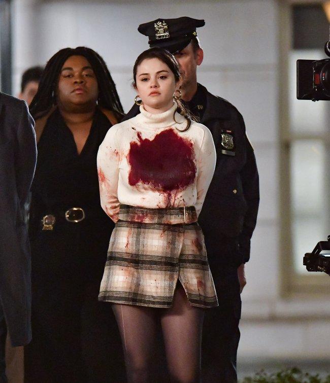 Selena Gomez aparece com uma macha de sangue em seu sueter bege de bola alta, sendo escoltada pela polícia, com as mãos para trás no set de filmagens da série