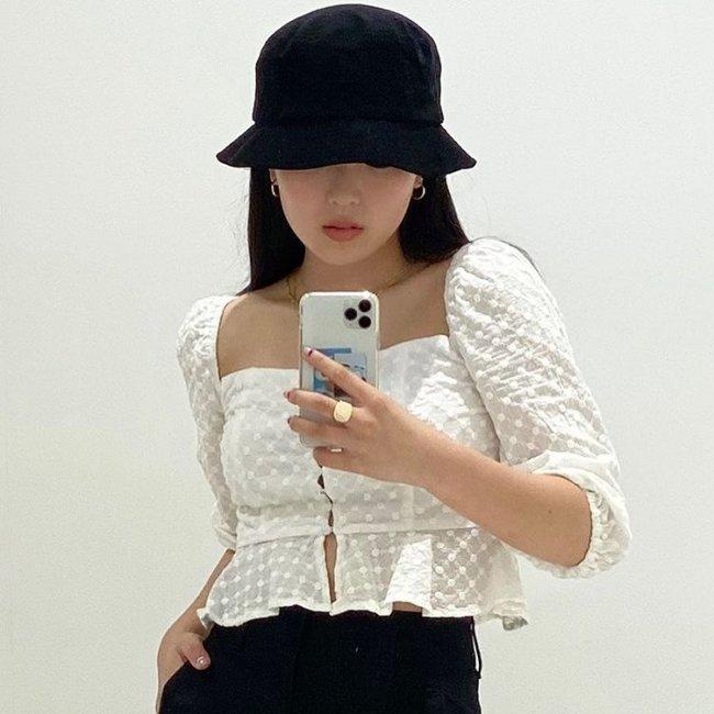 Hina, do grupo Now United, com Bucket Hat preto, usando blusa com manga bufante branca, foto da cintura para cima, mostrando o celular e com uma das mãos no bolso.
