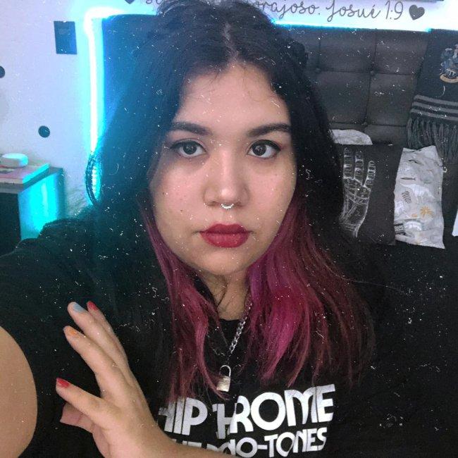 Jovem com uma das mãos apoiadas no braço, fazendo um selfie mostrando seu cabelo com corte médio, meio preso, exibindo suas mechas cor de rosa.